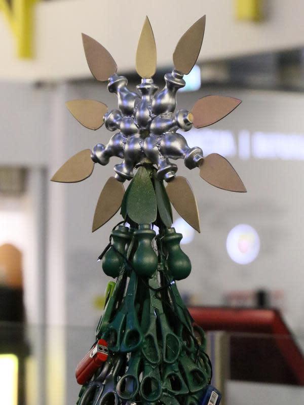 Bintang di puncak pohon Natal yang dirakit dari barang-barang sitaan di Bandara Vilnius, Lithuania pada 12 Desember 2019. Pohon Natal ini juga dilengkapi bintang keemasan di bagian atas yang dibuat dari pisau keju yang disusun memutar dan dicat emas . (Photo by Petras Malukas / AFP)