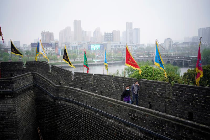People wearing face masks walk on an ancient city wall in Jingzhou, after the lockdown was eased in Hubei
