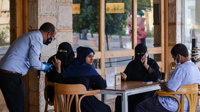 Pelayan mengenakan sarung dan masker melayani pelanggan di sebuah kafe di ibu kota Arab Saudi, Riyadh (21/6/2020). (AFP Photo/Fayez Nureldine)
