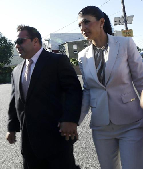 "Teresa Giudice, 41, right, and her husband Giuseppe ""Joe"" Giudice, 43, of Montville Township, N.J., walk toward Martin Luther King, Jr. Courthouse before a court appearance, Tuesday, July 30, 2013, in Newark, N.J. The two stars of the ""Real Housewives of New Jersey"" were indicted Monday on federal fraud charges, accused of exaggerating their income while applying for loans before their TV show debuted in 2009, then hiding their improving fortunes in a bankruptcy filing after their first season aired. They are charged in a 39-count indictment with conspiracy to commit mail and wire fraud, bank fraud, making false statements on loan applications and bankruptcy fraud. (AP Photo/Julio Cortez)"