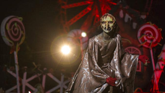 Seorang aktor berpakaian seperti penyihir tampil di taman hiburan horor Hopi Hari, pinggiran Vinhedo, Sao Paulo, Brasil, Jumat (4/9/2020). Karena pembatasan akibat COVID-19, taman hiburan horor Hopi Hari menampilkan pertunjukan secara drive-thru. (AP Photo/Carla Carniel)