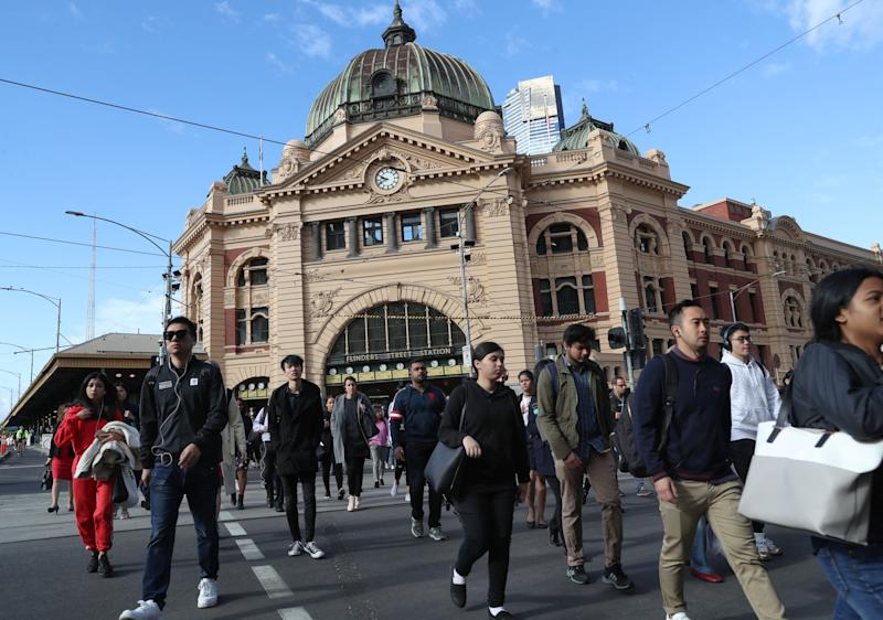 Pedestrians cross the intersection in front of Flinders Street Station in Melbourne.