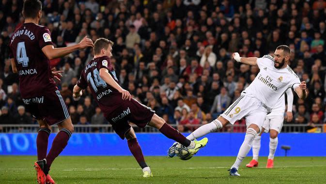 Penyerang Real Madrid, Karim Benzema berebut bola dengan Gelandang Celta Vigo, Filip Bradaric pada pertandingan lanjutan La Liga Spanyol di stadion Santiago Bernabeu di Madrid, Spanyol, Minggu, (16/2/2020). Madrid bermain imbang 2-2 atas Celta Vigo. (AFP/Pierre-Philippe Marcou)