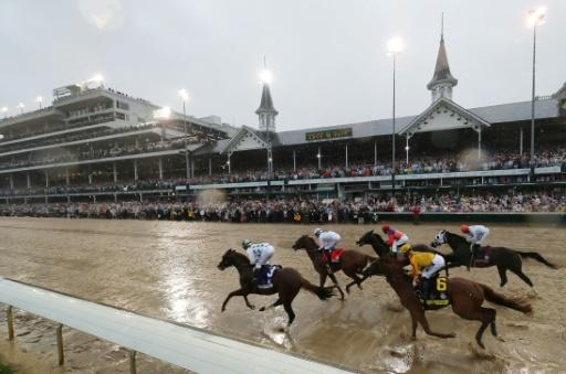 Promises Fulfilled (near post), ridden by Corey Lanerie and Justify, ridden by Mike Smith, lead the field into the first turn during the Kentucky Derby
