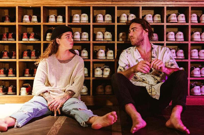 Australian singers Matt Corby and Tash Sultana sit in front of bowling shoes.