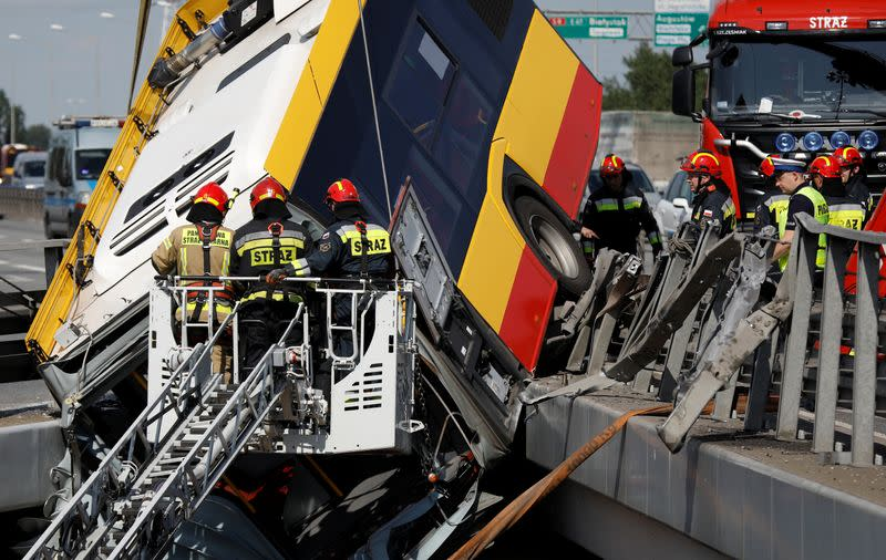 Emergency personnel work at the site of a crash after a city bus fell off a motorway bridge in Warsaw