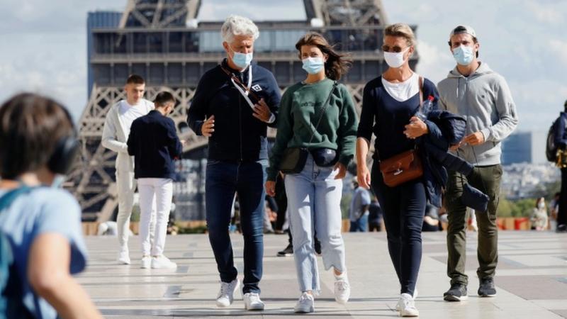 Orang-orang yang mengenakan masker berjalan di lapangan Trocadero dekat Menara Eiffel di Paris.