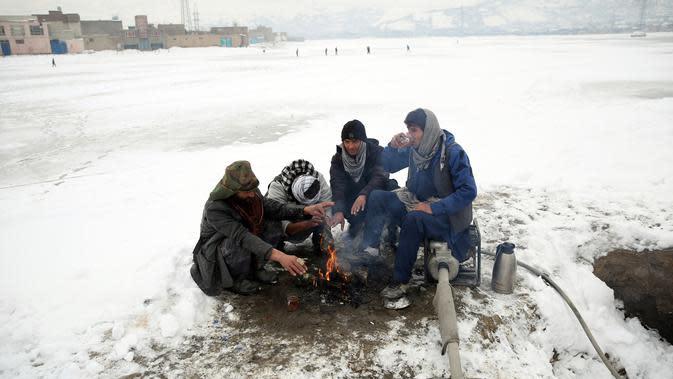 Sejumlah orang duduk di sekitar api untuk menghangatkan diri setelah hujan salju lebat di Kabul, Afghanistan, Selasa (14/1/2020). Sebanyak 24 orang dilaporkan tewas akibat cuaca buruk yang melanda Afghanistan. (AP Photo/Rahmat Gul)