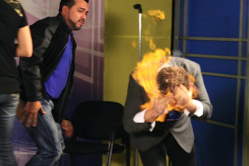 """In this picture released by American magician Wayne Houchin, Dominican TV presenter Franklin Barazarte, left, watches as Houchin's head burns while taping """"Closer To The Stars"""" TV program in Santo Domingo, Dominican Republic, Monday, Nov. 26, 2012. Houchin, of Chico, California, is receiving treatment for burns after the incident where Barazarte lit his head on fire with a flammable cologne. (AP Photo)"""