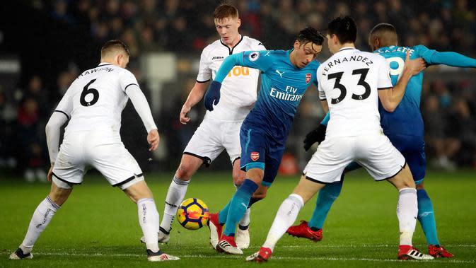 Pemain Arsenal, Mesut Ozil berusaha merebut bola dengan kawalan pemain Swansea City dalam laga pekan ke-25 Premier League 2017-2018 di Liberty Stadium, Selasa (30/1). Arsenal dipaksa menyerah Swansea City 1-3. (Nick Potts/PA via AP)