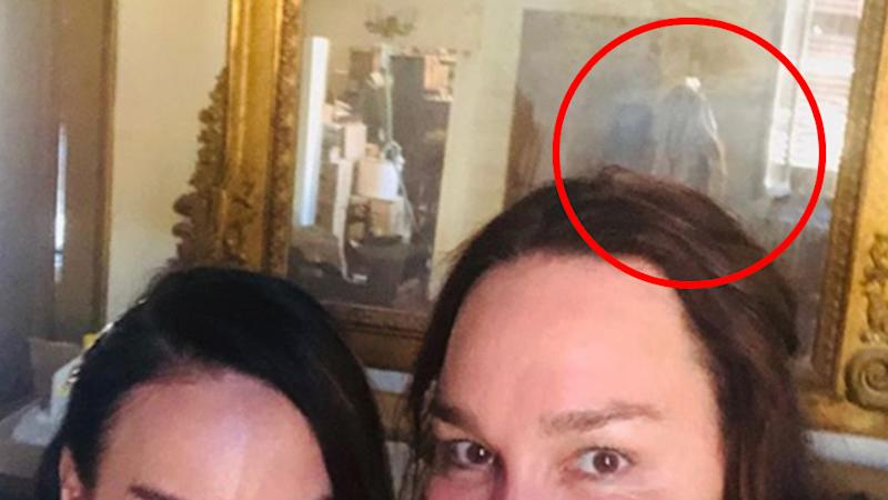 A selfie of radio host Kate Langbroek and her friend that shows a ghostly figure in the background.
