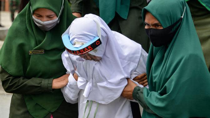 Polisi syariat membawa terpidana kasus zina untuk menjalani hukuman cambuk di halaman Masjid Al-Munawarah, Kota Jantho, Aceh Besar, Jumat (9/4/2020). Pasangan terpidana yang terbukti melanggar Syariat Islam dalam kasus zina itu masing masing menjalani sebanyak 100 cambuk. (CHAIDEER MAHYUDDIN/AFP)
