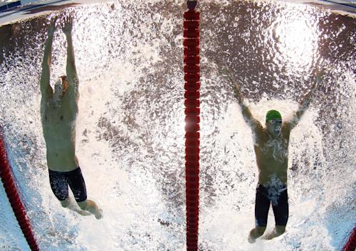 FILE - In this Friday, Aug. 3, 2012 file photo, United States' Michael Phelps, left, touches the wall as South Africa's Chad le Clos closes in for second place during the men's 100-meter butterfly final at the Aquatics Centre in the Olympic Park during the 2012 Summer Olympics in London. (AP Photo/Mark J. Terrill, File)