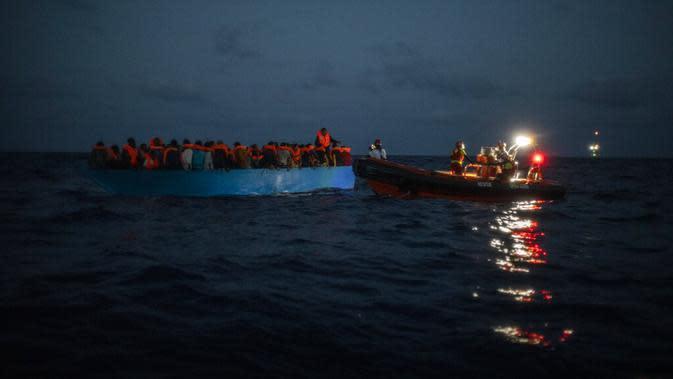 LSM Spanyol Open Arms menolong imigran di Laut Mediterania, Selasa (8/9/2020). Puluhan imigran termasuk wanita dan anak-anak asal Mesir, Maroko, Somalia, dan Sierra Leone menghabiskan lebih dari 20 jam saat melarikan diri dari Libya dengan kapal kayu. (AP Photo/Santi Palacios)