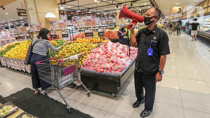 Security melakukan sosialisasi dengan megaphone di supermarket AEON Mall BSD City, Tangerang, Rabu (3/6/2020). Sosialisasi untuk pengunjung bertujuan agar tetap menjaga jarak interaksi dan selalu kenakan masker selama berbelanja guna mencegah penyebaran Covid-19. (Liputan6.com/Fery Pradolo)