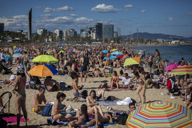 FILE - In this Saturday, June 13, 2020 file photo, people enjoy the warm weather on the beach in Barcelona, Spain. European Union envoys are close to finalizing a list of countries whose citizens will be allowed back into Europe once it begins lifting coronavirus-linked restrictions. The United States appears almost certain not to make the list, as new infections surge and given that President Donald Trump has imposed a ban on European travelers. (AP Photo/Emilio Morenatti, File)