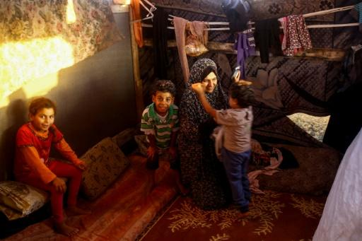 Noor and her children inside the family's shack near the beach in Gaza City