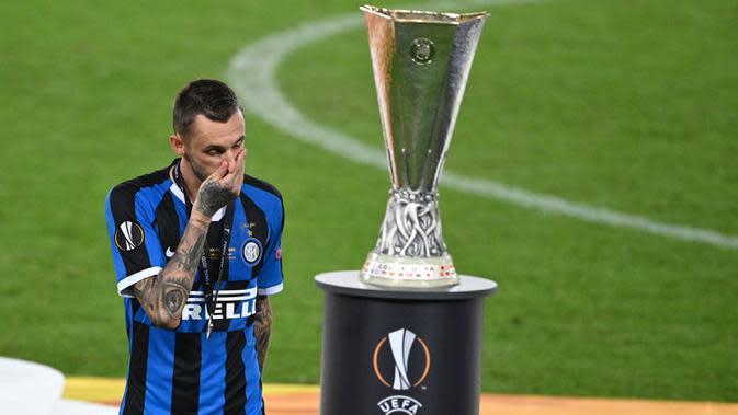 Pemain Inter Milan, Marcelo Brozovic, berjalan melewati trofi Liga Europa 2019/2020 di Stadion RheinEenergie, Sabtu (22/8/2020) dini hari WIB. Inter Milan kalah 2-3 atas Sevilla. (AFP/ Ina Fassbender/pool)
