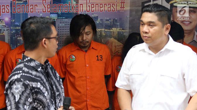 Vokalis grup band Zivilia, Zulkifli alias Zul (tengah) saat diperlihatkan petugas Ditresnarkoba Polda Metro Jaya, Jakarta, Jumat (8/3). Zul ditangkap berikut barang bukti 9,54 kilogram sabu dan 24.000 butir ekstasi. (Liputan6.com/Helmi Fithriansyah)