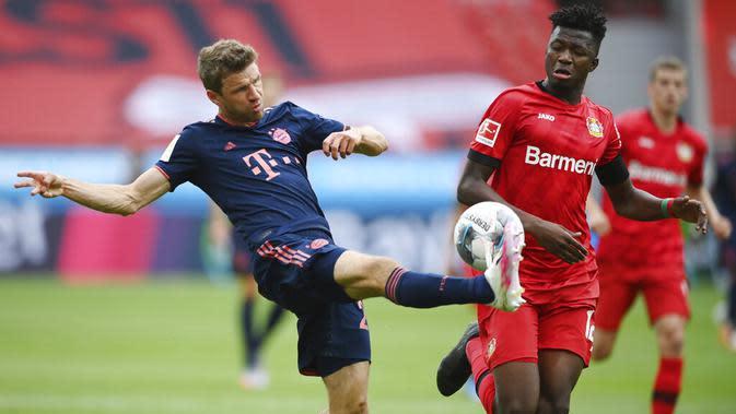 Striker Bayern Munchen, Thomas Mueller, melepaskan tendangan saat melawan Bayer Leverkusen pada laga Bundesliga di BayArena, Sabtu (6/6/2020). Bayern Munchen menang 4-2 atas Bayer Leverkusen. (AP/Matthias Hangst)