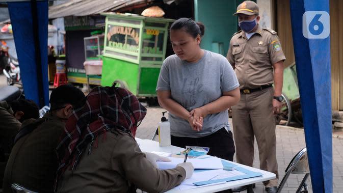 Petugas mendata seorang perempuan yang tidak mengenakan masker di Tangerang, Kamis (14/5/2020). Pemkot Tangerang melakukan tindakan bagi pelanggar PSBB dengan membawa mereka ke kantor Kecamatan Karawaci Baru untuk dilakukan pemeriksaan cepat COVID-19 (Rapid Test). (Liputan6.com/Angga Yuniar)