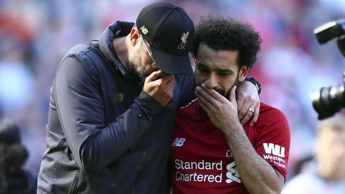 Pelatih Liverpool, Juergen Klopp, berbincang dengan Mohamed Salah usai gagal meraih gelar juara Premier League di Stadion Anfield, Minggu (12/5). Liverpool menyudahi musim ini di peringkat kedua klasemen Premier League dengan nilai 97. (AP/Dave Thompson)