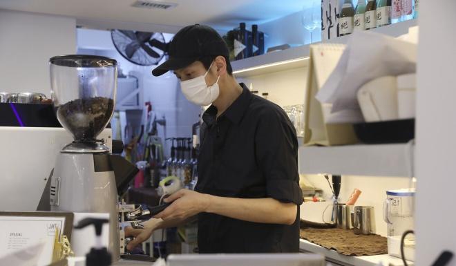 An employee works at JMT Coffee, a yellow shop in Sai Ying Pun. Photo: K. Y. Cheng