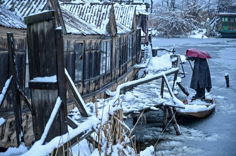 A man removes snow from his boat on the banks of Dal Lake in Srinagar in India