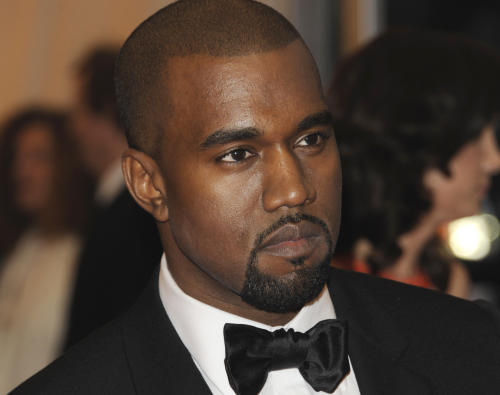 """In this Monday, May 7, 2012 photo, Kanye West arrives at the Metropolitan Museum of Art Costume Institute gala benefit, celebrating Elsa Schiaparelli and Miuccia Prada, in New York. West closed the three-day Governors Ball on New York's Randall's Island with a set that featured his familiar hits as well as a batch of new, darker tracks from his upcoming album. West kicked off his set Sunday night, June 9, 2013, with the song """"Black Skinhead,"""" with flashing visuals in the background, including the words """"not for sale."""" He later performed """"New Slaves."""" Both tracks will appear on """"Yeezus,"""" his sixth album out June 18. (AP Photo/Evan Agostini)"""