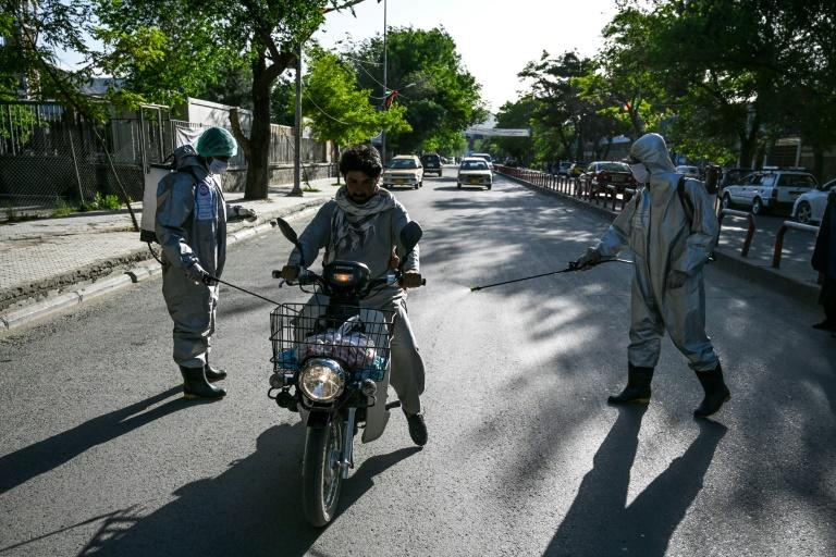 Volunteers wearing protective gear spray disinfectant on a motorcyclist as a preventive measure against the COVID-19 coronavirus in Kabul