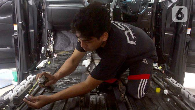 Pekerja membersihkan kelistrikan mobil yang terkena banjir di bengkel Detailing, Shop, Garage (DSG) di kawasan Pondok Pinang, Jakarta, Kamis (9/1/2020). Pascabanjir yang melanda Jakarta pada 1-3 Januari lalu, tercatat 35 mobil memasuki bengkel ini untuk diperbaiki. (merdeka.com/Arie Basuki)