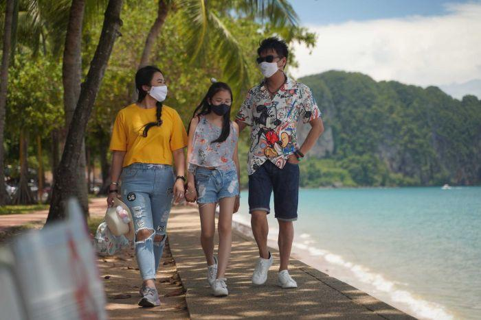 Three people wearing colourful clothes and masks walk along a sidewalk next to a beach with mountains in the background.