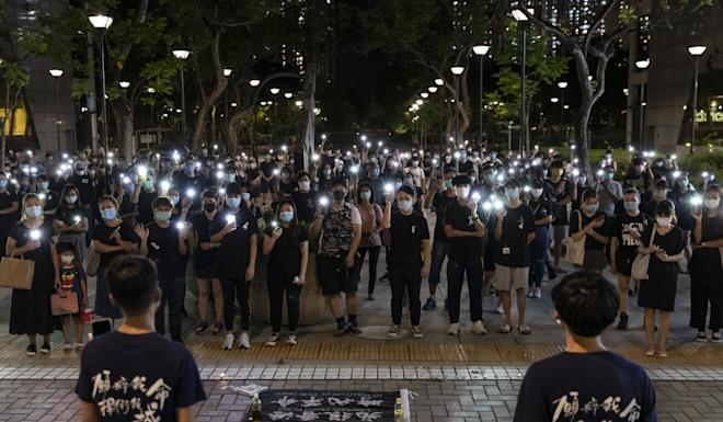 Pro-democracy protesters light up their mobile phones at a memorial on Monday for a protester who fell to his death during the protests last year. Photo: ZUMA Wire via dpa