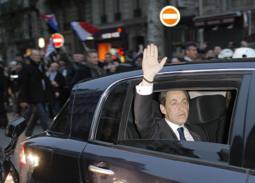 Outgoing French President Nicolas Sarkozy waves from his car as he leaves after addressing supporters at his Union for a Popular Movement (UMP) party headquarters after the the preliminary results of the second round of the presidential elections were announced in Paris Sunday May 6, 2012. Socialist Francois Hollande defeated Sarkozy on Sunday to become France's next president, Sarkozy conceded defeat minutes after the polls closed. (AP Photo/Thibault Camus)