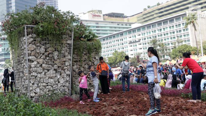 Anak-anak berfoto di area taman dekat Instalasi Gabion saat CFD di kawasan Bundaran Hotel Indonesia, Jakarta, Minggu (25/8/2019). Pengadaan Instalasi Gabion ini menggunakan Anggaran Pendapatan dan Belanja Daerah (APBD) Dinas Kehutanan DKI sebesar Rp 150 juta. (Liputan6.com/Helmi Fithriansyah)