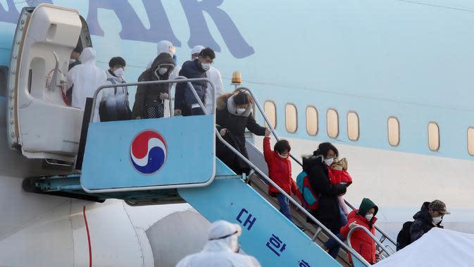 Warga Korea Selatan yang dievakuasi dari dari Wuhan, China, menuruni pesawat charter di Bandara Internasional Gimpo di Seoul pada Jumat (31/1/2020). Pesawat sewaan tersebut membawa pulang 367 warga negara Korea Selatan dari Wuhan, pusat wabah virus corona. (Kim Kyun-hyun/Newsis via AP)
