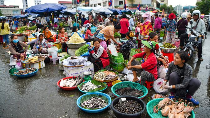 Pedagang memajang dagangannya saat mereka menunggu pelanggan di pasar di Phnom Penh (24/7/2020). Kota ini memiliki penduduk sekitar 1 juta jiwa, sementara seluruh penduduk Kamboja adalah 11,4 juta jiwa. . (AFP/Tang Chhin Sothy)