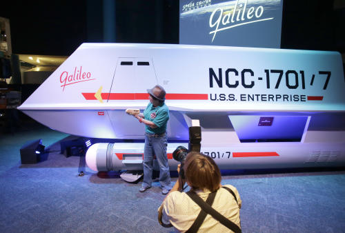 "Candy Torres is photographed standing in front of the restored space shuttle Galileo from the 1960's television show Star Trek holding her plastic toy version of the vehicle at Space Center Houston Wednesday, July 31, 2013, in Houston. The restored shuttlecraft that crash-landed on a hostile planet in the 1967 episode ""The Galileo Seven"" was officially unveiled at the Space Center Houston before a crowd of die-hard Star Trek fans. (AP Photo/Pat Sullivan)"