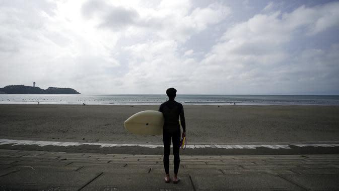 Seorang peselancar melihat pantai Katase-kaigan yang berangin, Fujisawa, Prefektur Kanagawa, selatan Tokyo, Jepang, Kamis (24/9/2020). Badai Tropis Dolphin bergerak di sepanjang pantai Pasifik Jepang. (AP Photo/Eugene Hoshiko)