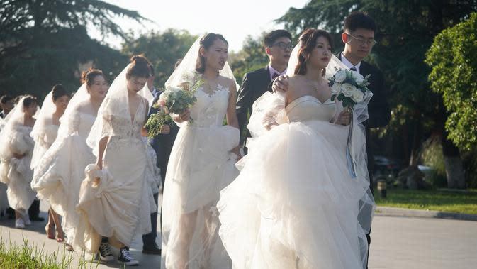 Beberapa pasangan pengantin bersiap untuk berfoto di Nanjing, Provinsi Jiangsu, China timur, (19/5/2020). Di antara pasangan pengantin baru itu terdapat beberapa pekerja medis yang menunda pernikahan mereka karena ikut berjuang memerangi pandemi COVID-19. (Xinhua/Ji Chunpeng)