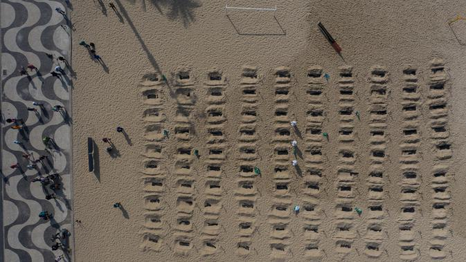 Aktivis menggali kuburan di pantai Copacabana, Rio de Janeiro, Kamis (11/6/2020). Aksi simbolis yang dilakukan oleh kelompok LSM Rio de Paz itu sebagai bentuk protes atas respons pemerintah Brasil dalam menangani pandemi Covid-19. (AP Photo/Leo Correa)