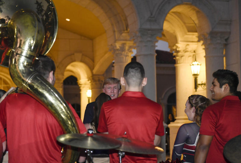 President Donald Trump talks with members of the Florida Atlantic University Marching Band after they performed during a Super Bowl party at the Trump International Golf Club in West Palm Beach, Fla., Sunday, Feb. 2, 2020. (AP Photo/Susan Walsh)