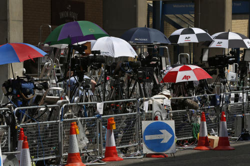 Members of the media shelter under umbrellas to shield themselves from the sun as they wait across St. Mary's Hospital exclusive Lindo Wing in London, Sunday, July 14, 2013. Media are preparing for royal-mania as Britain's Duchess of Cambridge is expected to give birth to the new third-in-line to the throne in mid-July, at the Lindo Wing. Cameras from all over the world are set to be jostling outside for an exclusive first glimpse of Britain's Prince William and the Duchess of Cambridge's first child. (AP Photo/Lefteris Pitarakis)