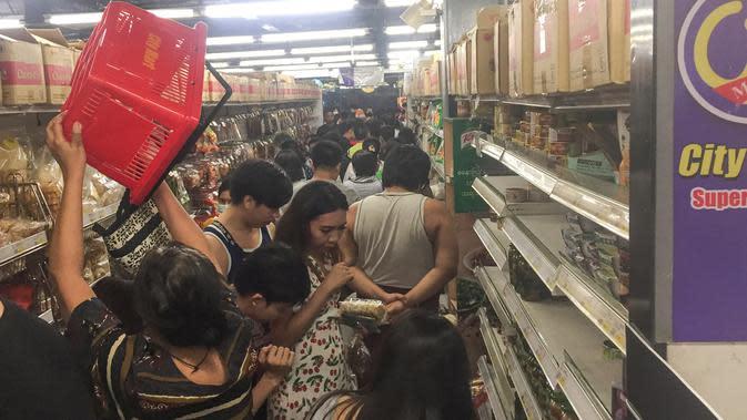 Orang-orang berbelanja makanan dan persediaan lainnya di supermarket 24 jam di Yangon, Selasa (24/3/2020). Tanggapi kasus pertama Corona COVID-19 pada Senin 23 Maret malam, warga Myanmar memadati pusat perbelanjaan untuk menyetok kebutuhan pokok dan persedian makanan. (AP/Thein Zaw)