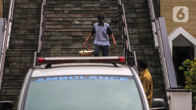 Seorang pria membawa bunga saat pelepasan jenazah Glenn Fredly di Gereja Sumber Kasih, Lebak Bulus, Jakarta, Kamis (9/4/2020). Kepergian Glenn Fredly menyisakan kepedihan mendalam bagi para sahabat. (Liputan6.com/Faizal Fanani)