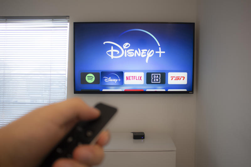 Calgary, Alberta. Canada Dec 5 2019: Person holds an Apple TV remote using the new Disney+ app on a Vizio TV. Disney+ video streaming service will exclusively show Star Wars: Jedi Template Challenge.