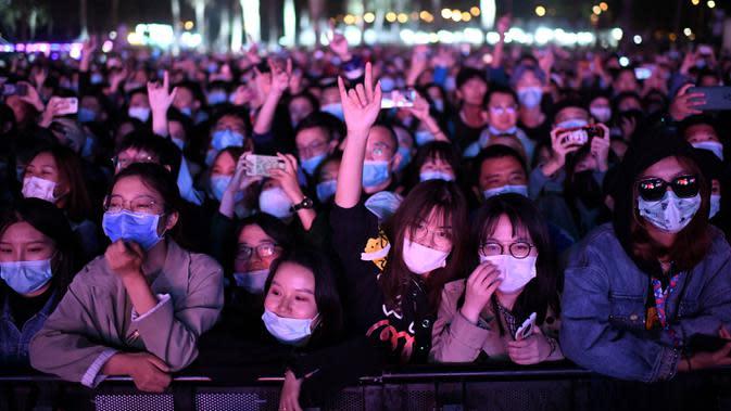 Orang-orang yang memakai masker menyaksikan penampilan sebuah band pada Festival Musik Rye yang digelar selama dua hari di Beijing pada 18 Oktober 2020. (Photo by Noel Celis / AFP)