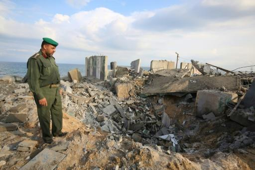 A Palestinian security man surveys the destruction from an Israeli air strike on the southern Gaza Strip town of Rafah on October 17, 2018