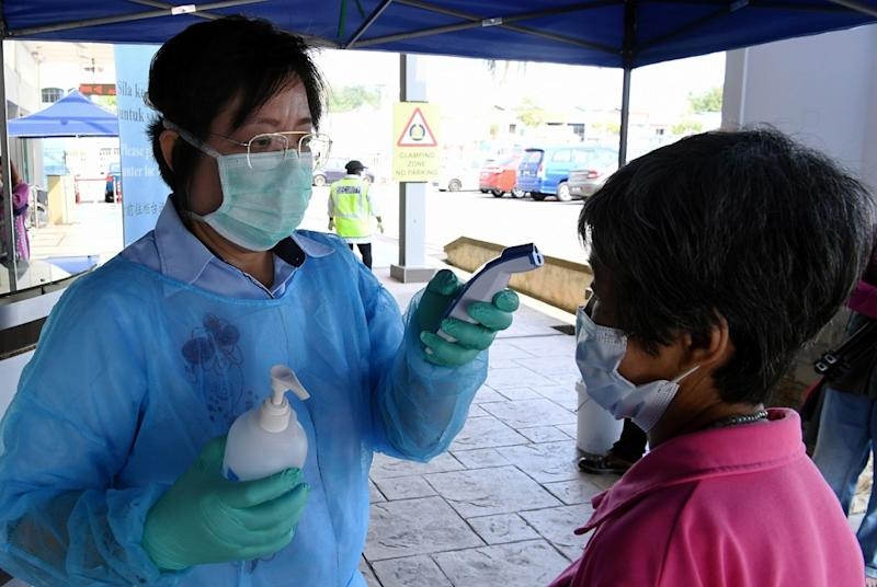 A health worker from Mawar Medical Centre checks the temperature of a visitor in Seremban March 20, 2020. — Bernama pic