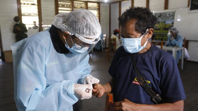 Pekerja medis mengumpulkan sampel tes COVID-19 dari seorang penduduk pribumi di Negara Bagian Roraima, Brasil (30/6/2020). Tim medis militer Brasil menyediakan perawatan medis bagi masyarakat pribumi mulai 30 Juni hingga 5 Juli, termasuk tes COVID-19. (Xinhua/Lucio Tavora)